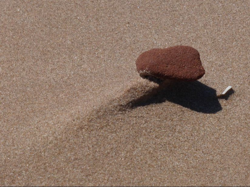 Red sandstone pebble on wind-scoured sand, PEI National Park, Canada.